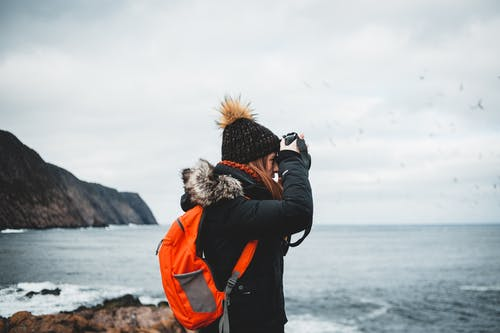 Side view of young female photographer in warm jacket and hat with bright orange backpack taking pictures of powerful stormy sea while standing on rocky shore during hiking trip