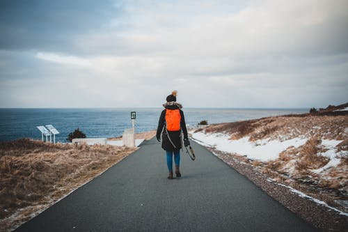 Anonymous female traveler walking on road near sea on winter day