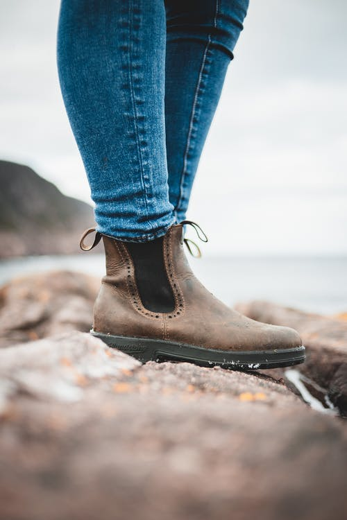 Side view of crop unrecognizable female traveler in jeans and boots standing on massive boulder and admiring sea on cloudy day