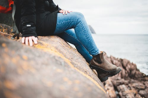 Crop unrecognizable woman sitting on rocky cliff edge and admiring wavy sea