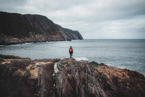 Unrecognizable traveler recreating on rocky cliff and admiring picturesque seascape