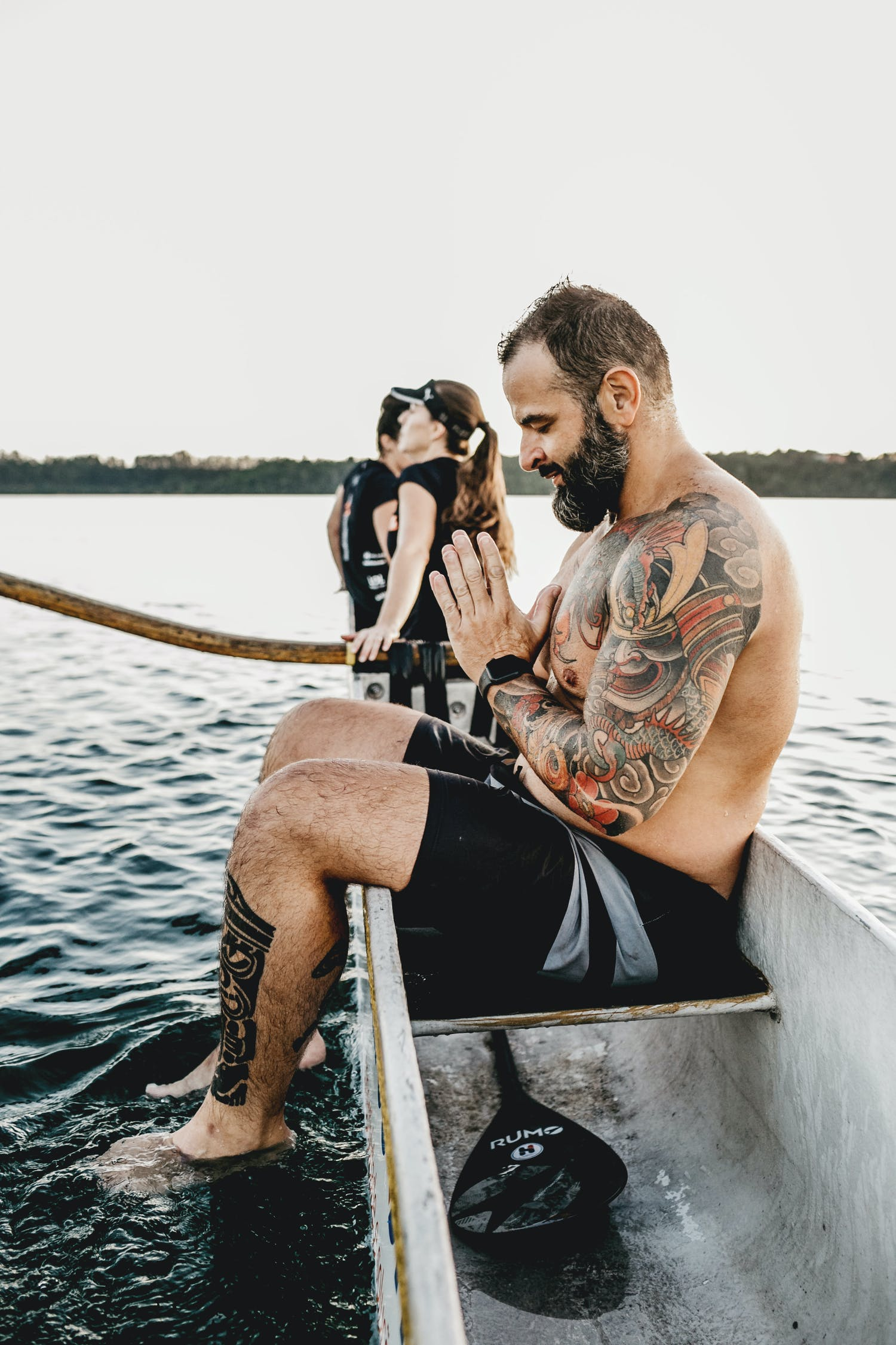 Tattooed sportsman praying in boat against unrecognizable friends on river