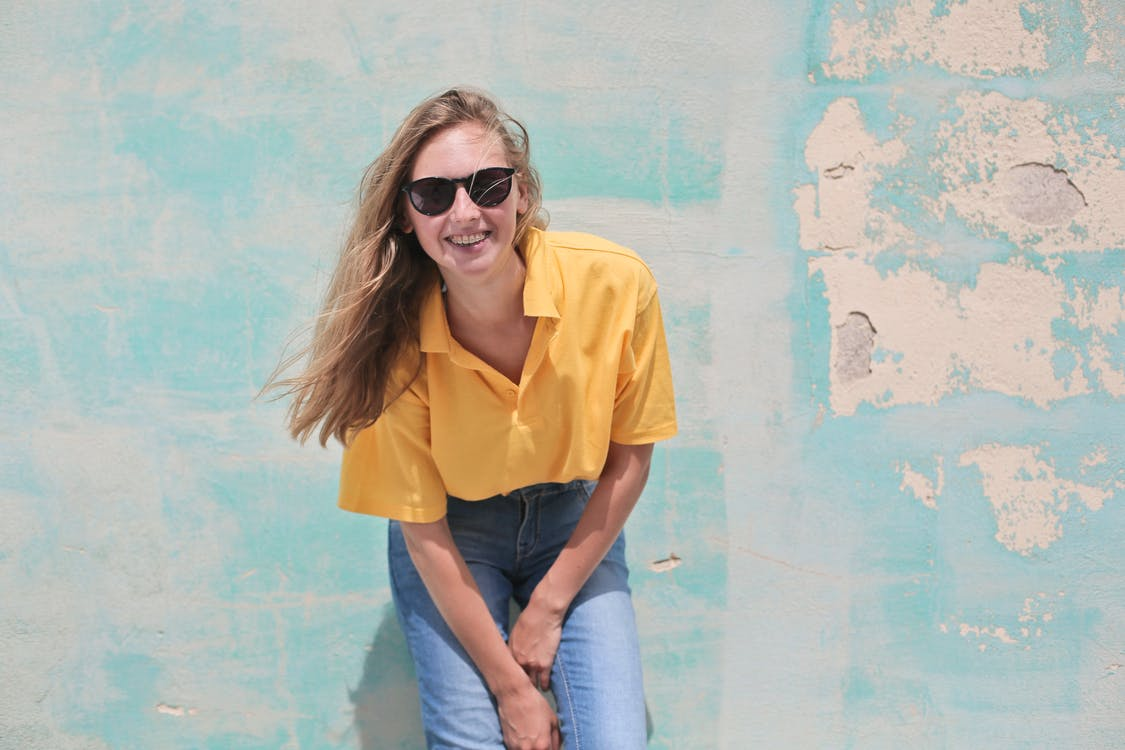 Woman Wearing Yellow Polo Shirt Standing in Front of Teal Concrete Wall