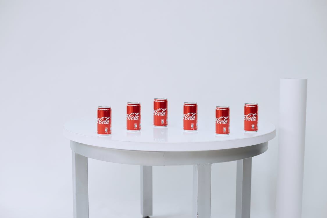 Red and White Plastic Containers on White Wooden Table