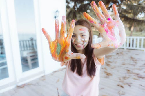 Woman in White Long Sleeve Shirt With Blue Paint on Her Hands