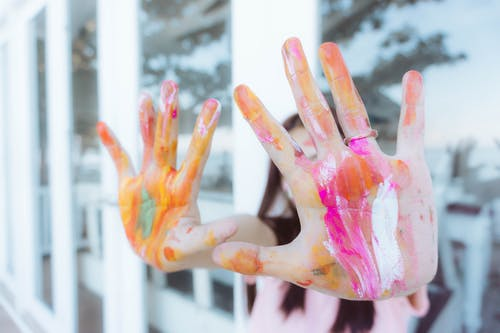 Persons Hand With Pink and White Paint