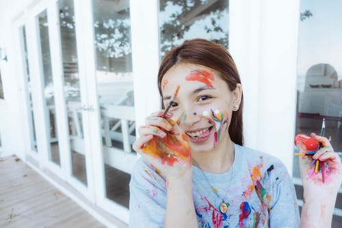 Girl in White and Blue Floral Crew Neck Shirt With Face Paint
