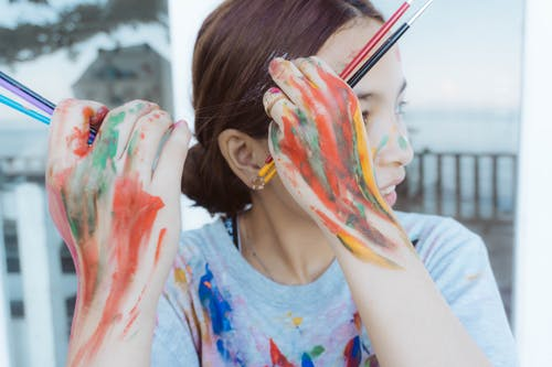 Woman in Blue Tank Top With Paint on Face