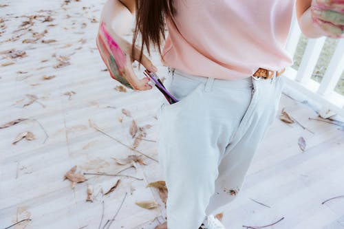 Woman in Pink Shirt and Blue Denim Jeans Standing on White Snow Covered Ground