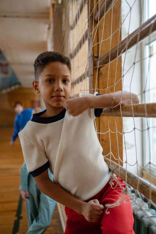 Boy in White and Blue Nike Crew Neck T-shirt Holding on Brown Net