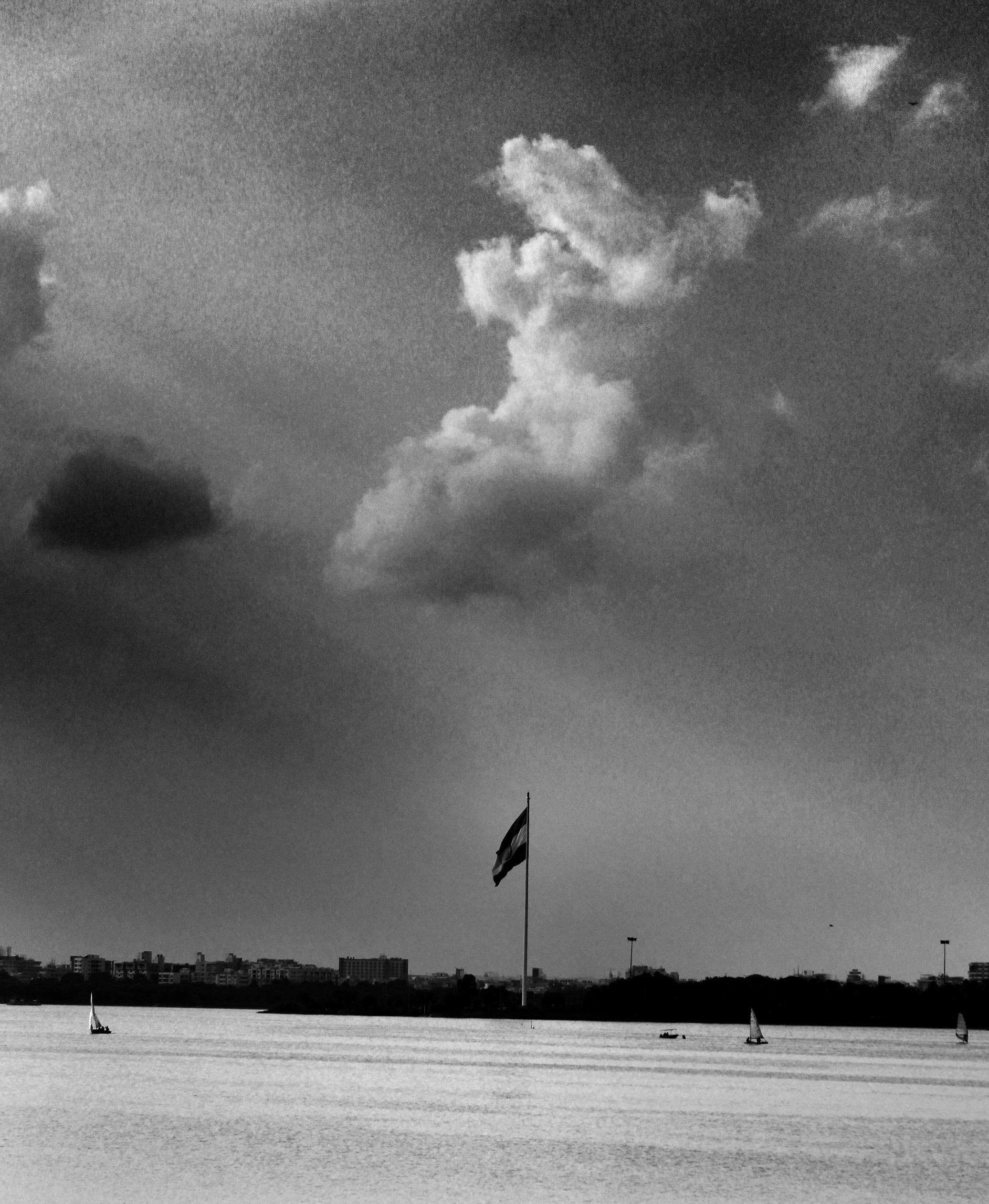 Grayscale Photo of Flag and Clouds