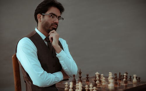 Serious ethnic man thinking over tactic of playing chess
