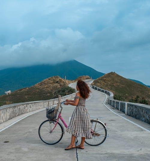 Woman in White Dress Riding Bicycle on Gray Concrete Bridge