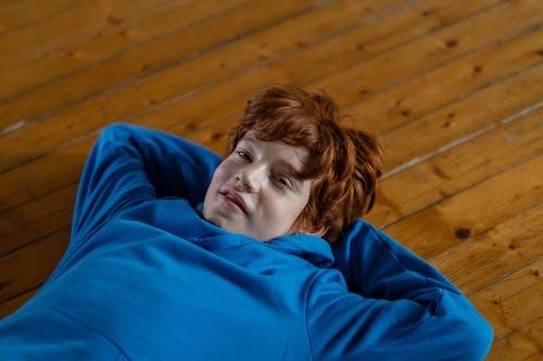 Woman in Blue Hoodie Lying on Brown Wooden Floor