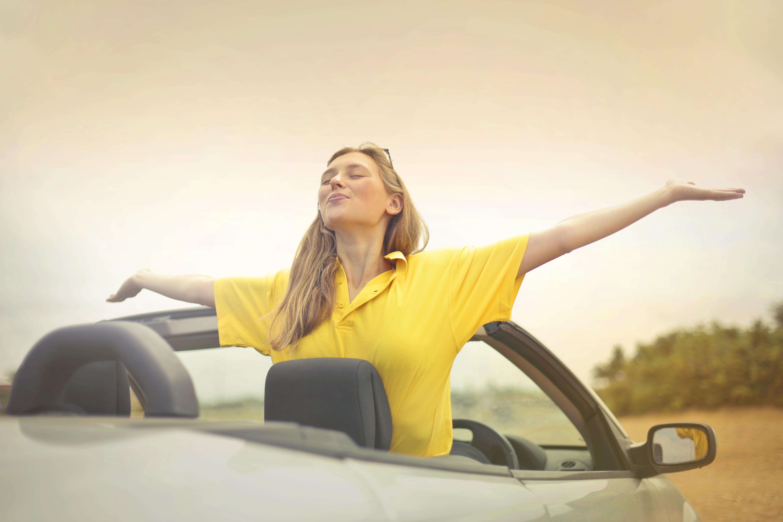 Woman Sitting on Car Under Gray Sky