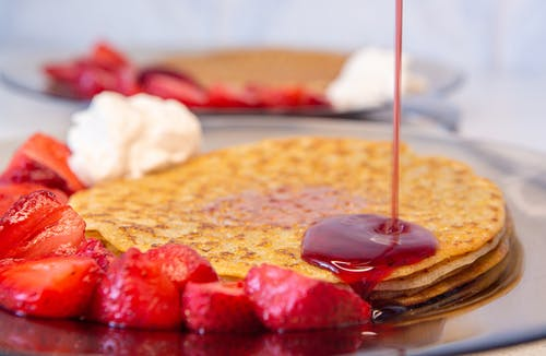 Selective Focus Photo of Strawberry Syrup being Poured on Pancakes