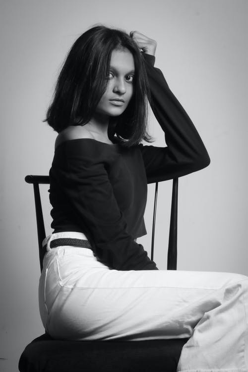 Black and white of young ethnic female in trendy outfit looking at camera on stool on white background of studio