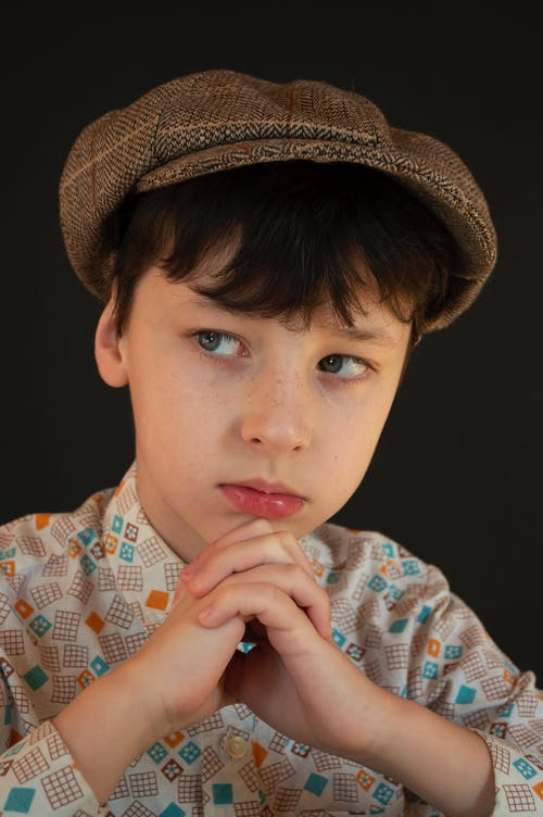 Charming boy in checkered shirt and brown hat looking away while sitting in studio