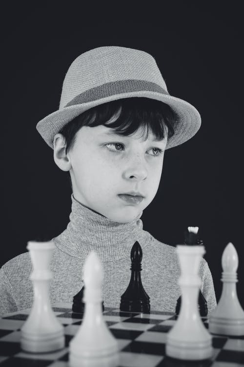 Grayscale Photo of a Boy in Fedora Hat beside a Chessboard
