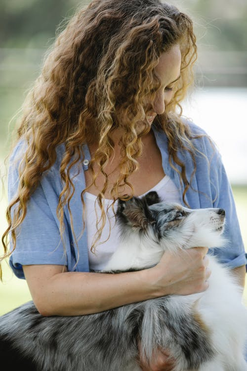 Smiling woman with curly hair stroking fluffy dog
