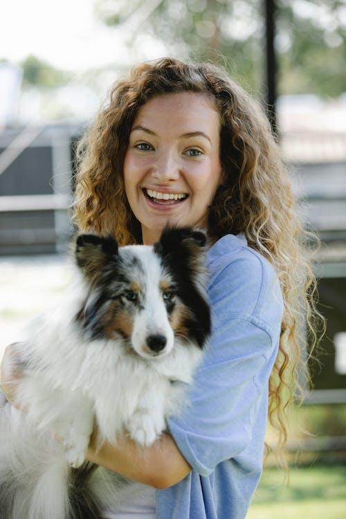 Smiling woman embracing Shetland Sheepdog in courtyard