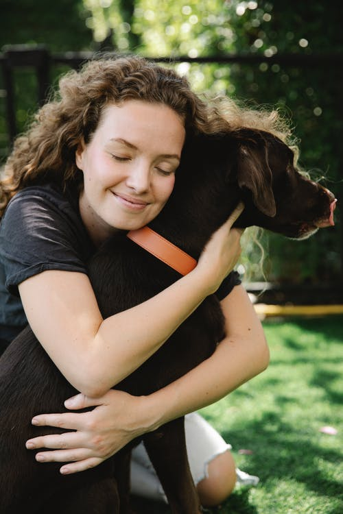Smiling female with closed eyes embracing pointing dog in collar while sitting on lawn in summer