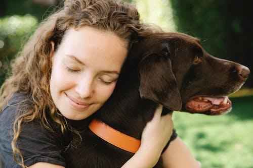 Mindful woman embracing bird dog on lawn