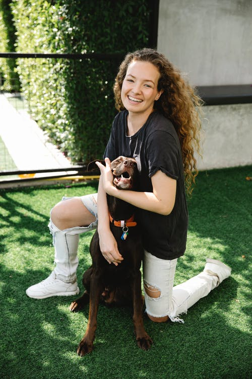 Cheerful female embracing pointing dog in collar with pendant while looking at camera on meadow in patio