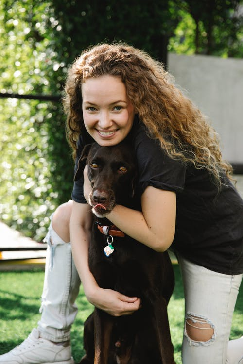 Content female with curly hair embracing gun dog licking muzzle while looking at camera on lawn