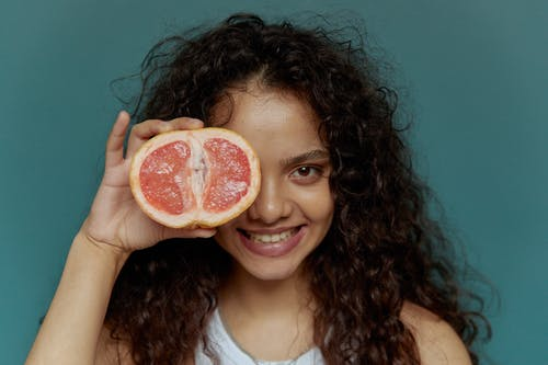 Close-Up Photo of a Woman with Curly Hair Holding a Sliced Grapefruit