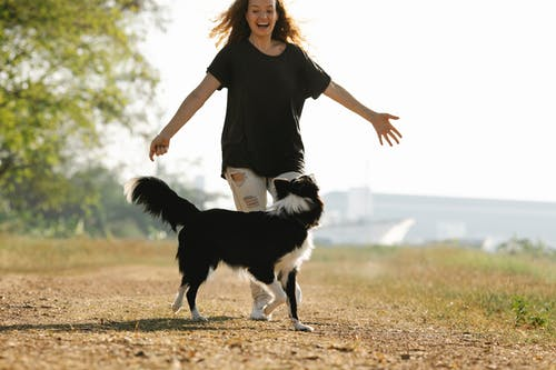 Happy woman running with Border Collie on rural road