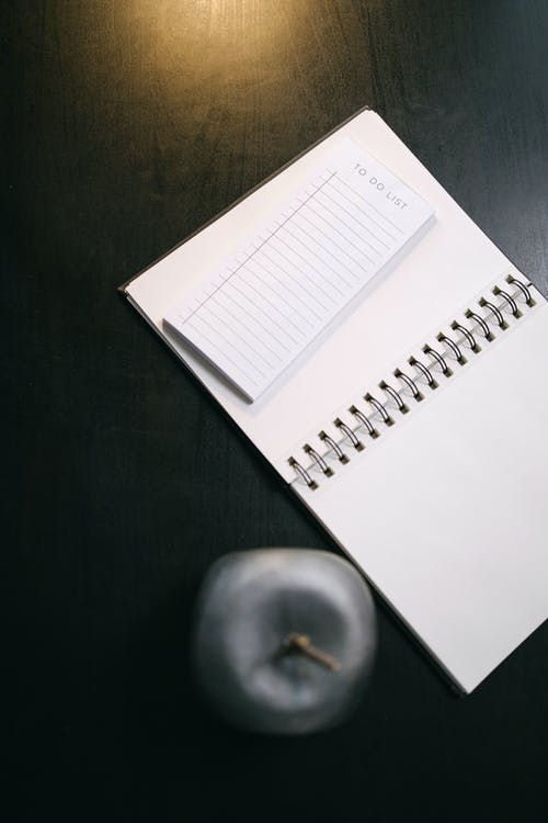 High-Angle Shot of a Notebook on a Black Surface