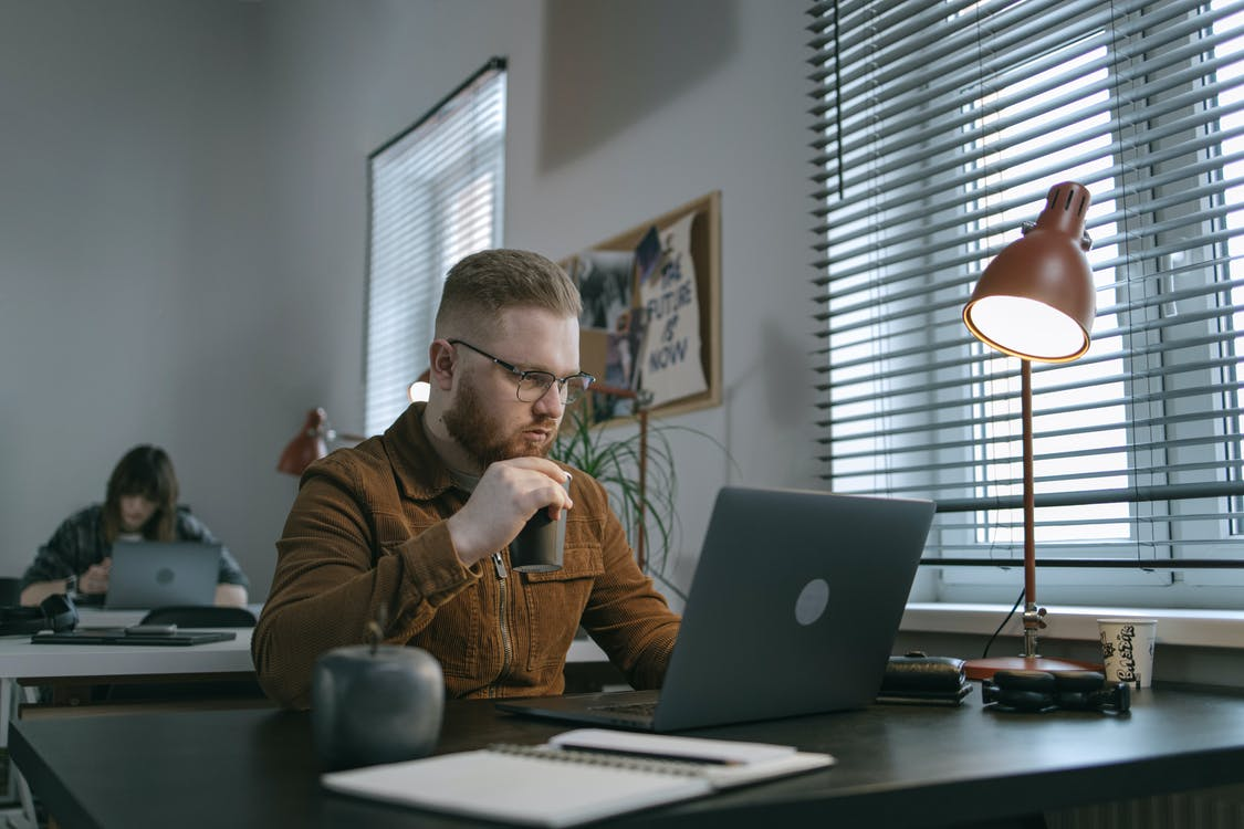Man in Brown Sweater Sitting in Front of Silver Macbook
