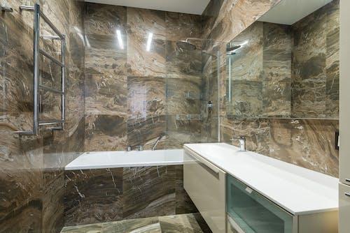 White Ceramic Bathtub Beside Brown Wall