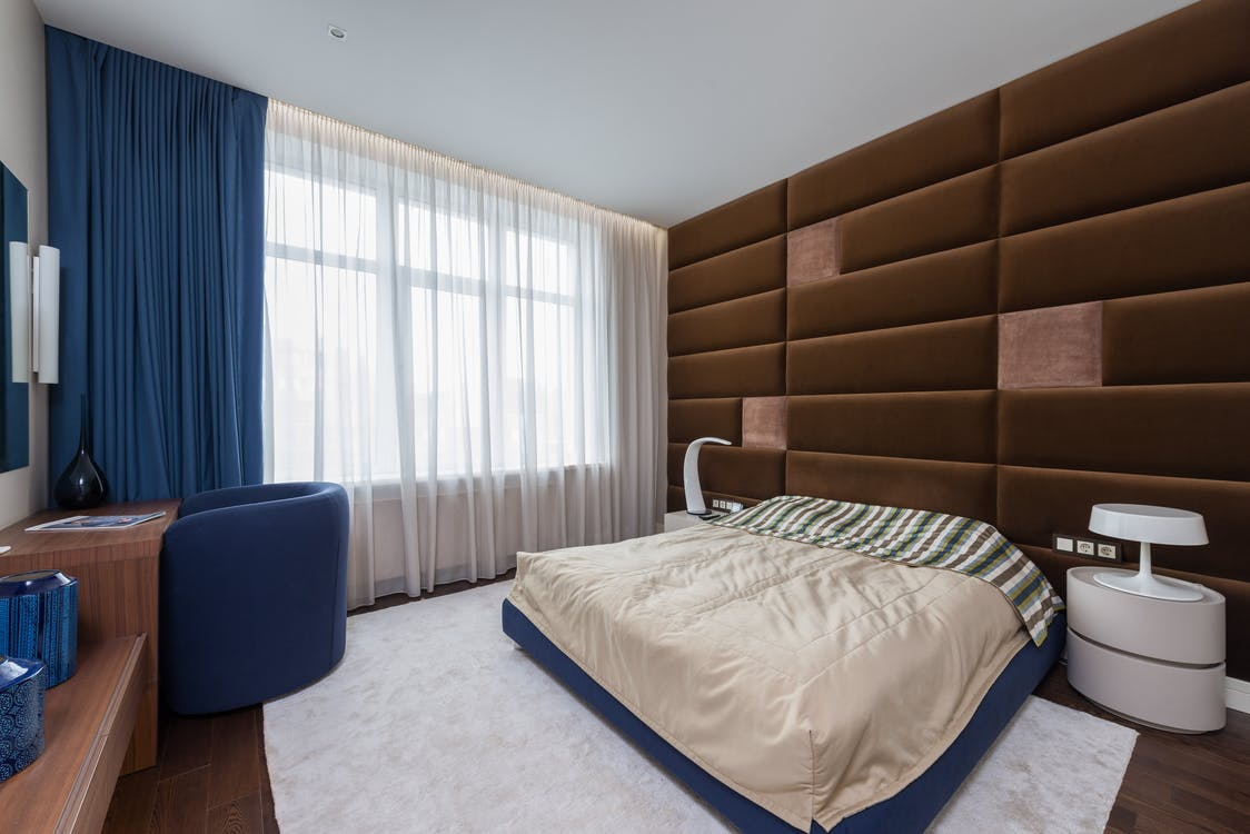 Comfortable bed with blanket placed at wall in contemporary light bedroom with wooden table and window with curtains at table