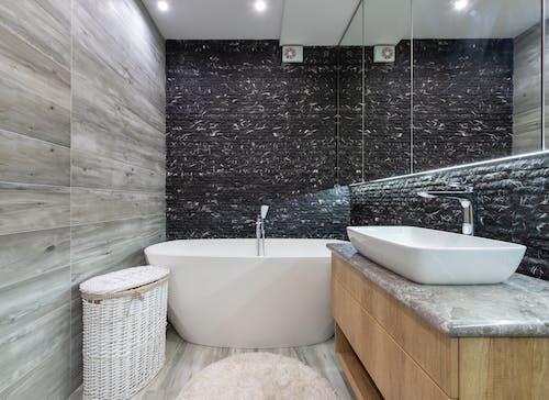 White Ceramic Bathtub Near  Black Textured Wall