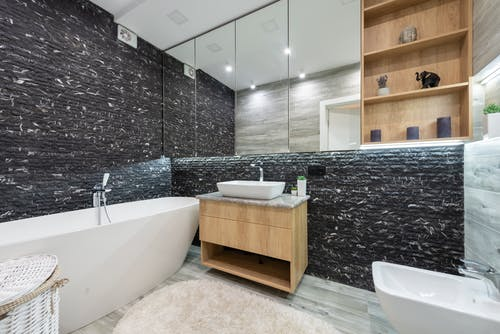Large mirror hanging on dark wall over sink and bathtub in spacious bathroom with wooden elements in apartment