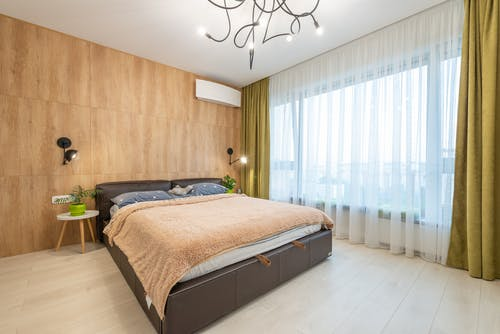 Empty bed in stylish bedroom in apartment