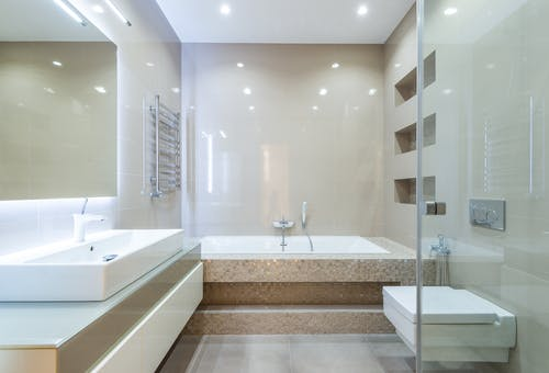 Empty spacious clean bathroom with tiled walls and light furniture in modern flat