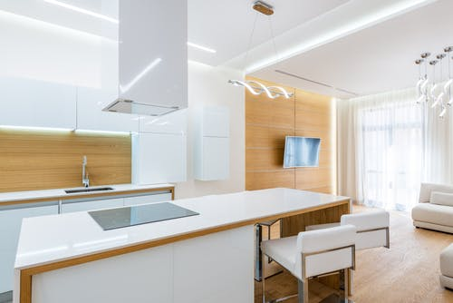 Stylish empty kitchen with expensive white furniture in spacious modern apartment in daylight