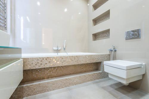 Bathtub placed near toilet in spacious bathroom with light walls in contemporary apartment