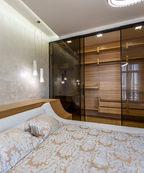 Luxury interior design of bedroom furnished with comfortable king sized bed and spacious wardrobe closet with glass doors and empty shelves