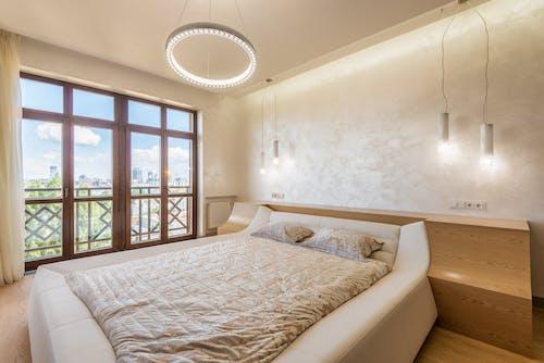 Trendy light bedroom with balcony