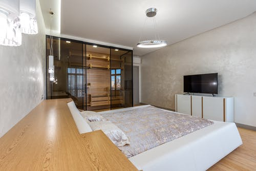 Bed with pillows placed against wall with TV on cupboard in spacious bedroom and glowing chandelier with wardrobe in apartment