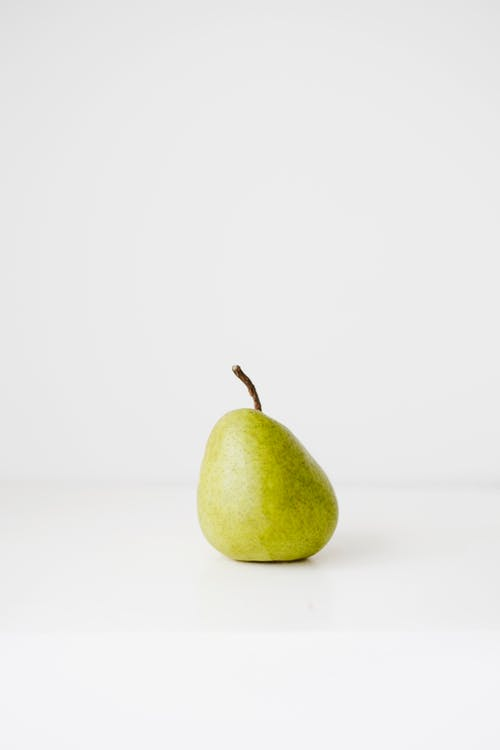 Fresh healthy pear on white surface