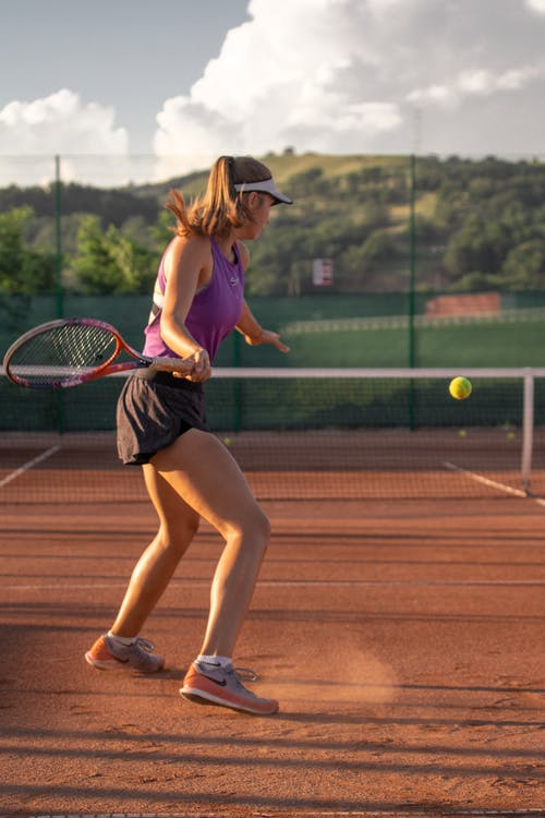 Side view full length of sportive female player in sportswear playing tennis while training on court