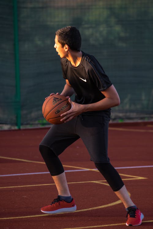 Focused young man playing streetball at sports ground