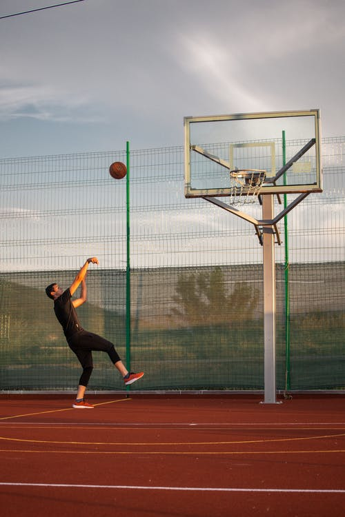 Young man throwing ball during basketball training