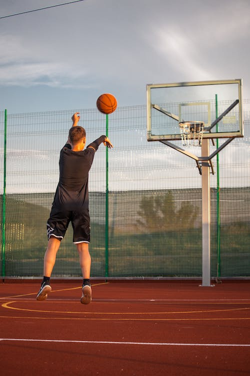 Full body back view of anonymous in activewear jumping while throwing ball in basketball backboard