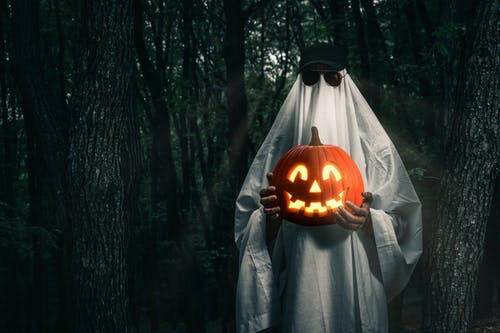 Person in Halloween costume with pumpkin